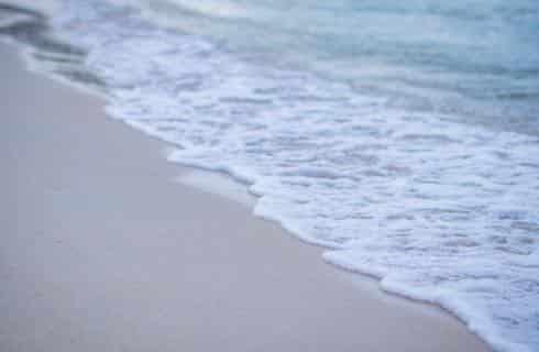 White foamy ocean water on a light sandy beach