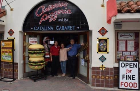 Store front of an Italian restaurant with people standing in front