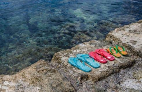 Teal, pink, yellow flipflops on large stone rock next to clear ocean water