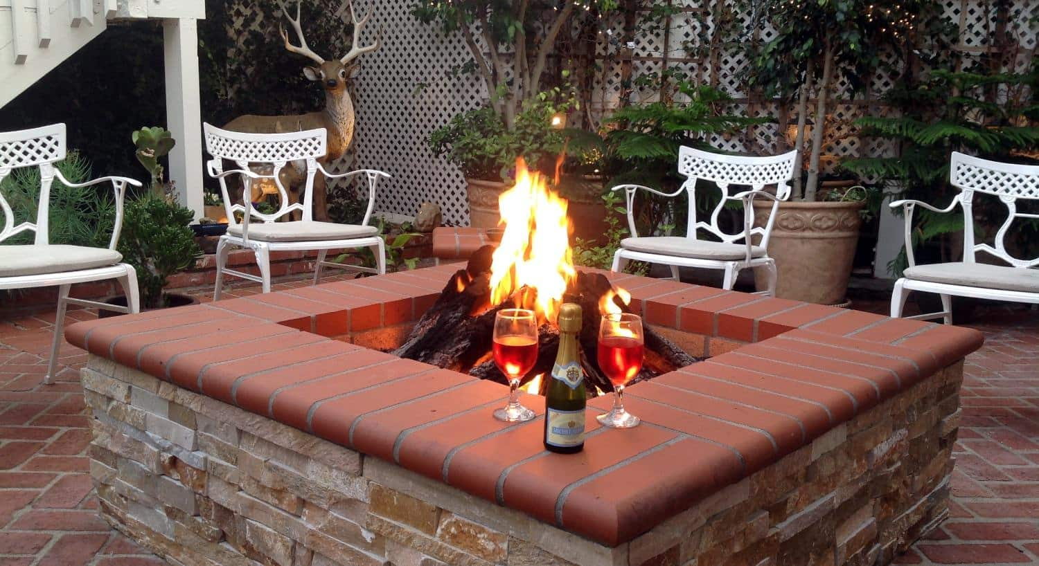 Fire pit made of red brick and light tan stone with a fire, white chairs, wine glasses, and wine