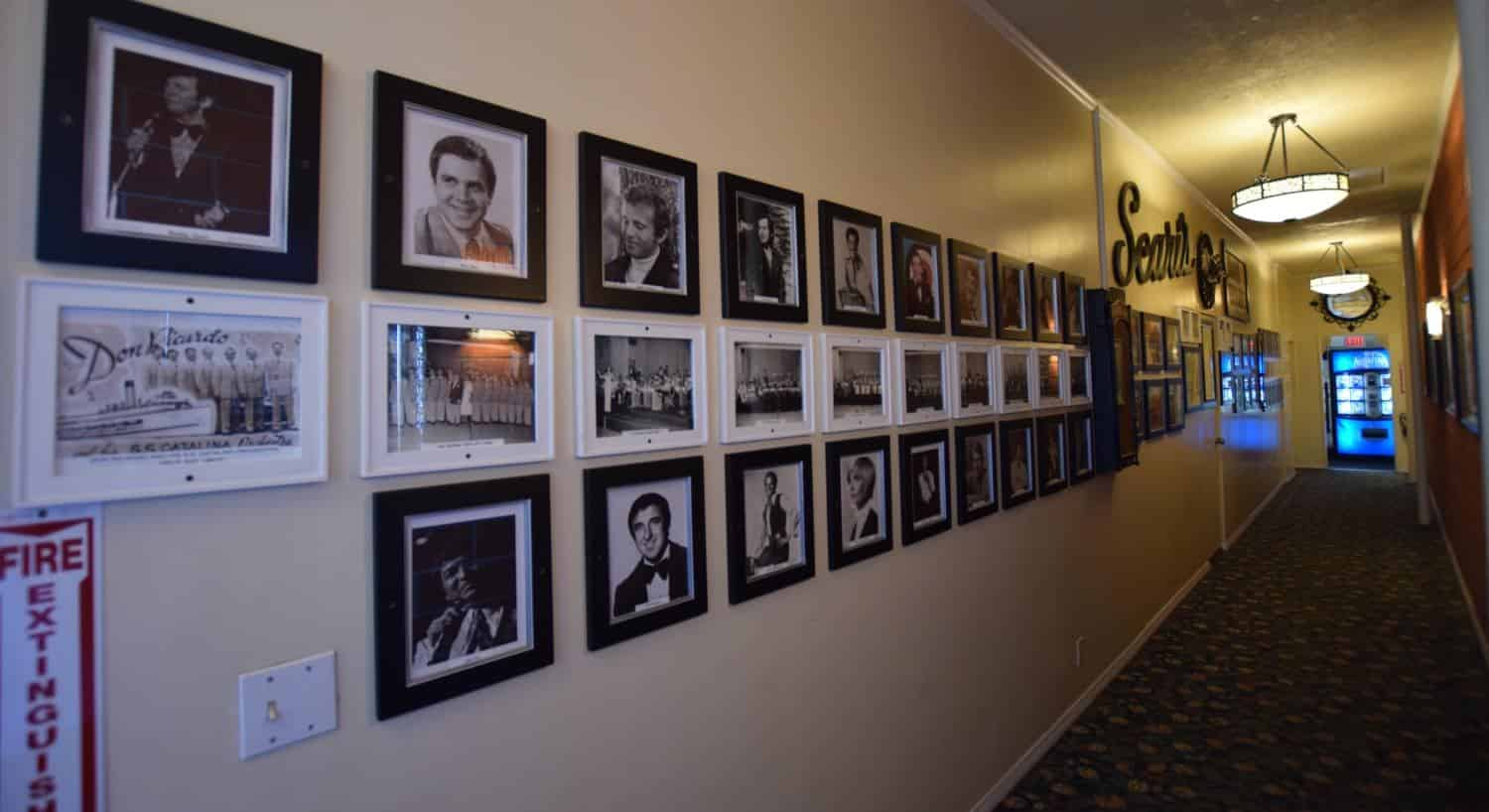 Long hallway with wall filled with photos of famous people