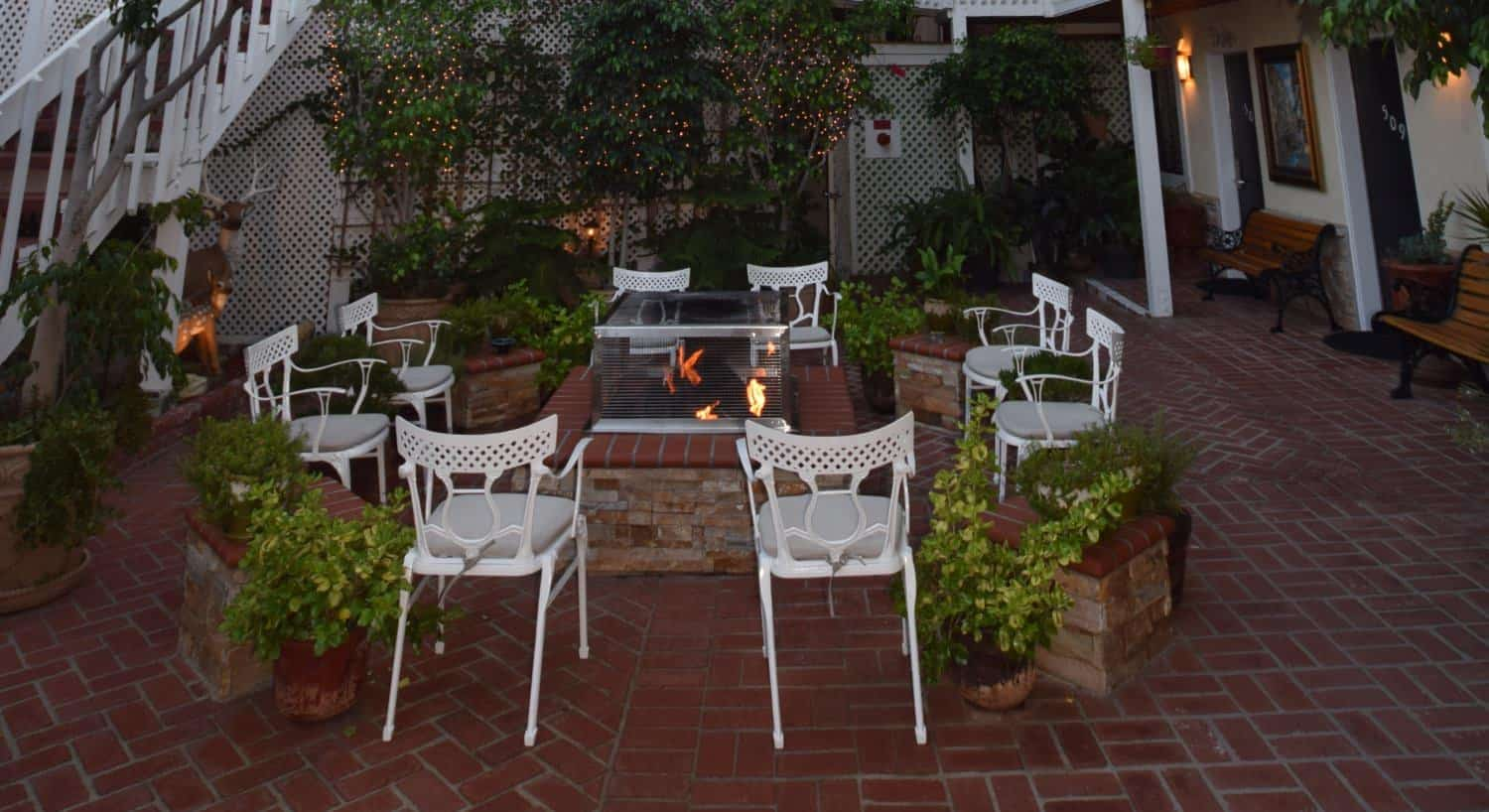 Courtyard patio with red brick, white chairs around a stone fire pit with greenery and sparkling lights around