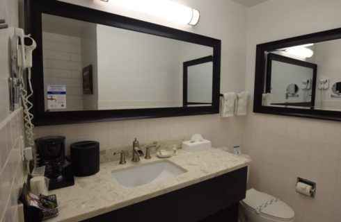 Bathroom with white-tiled wall, large mirror with dark wood frame, large vanity with granite countertop