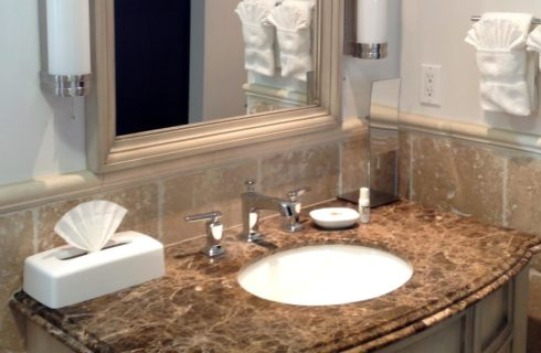 Bathroom vanity with dark and light brown granite counter top and mirror with cream-colored wooden frame