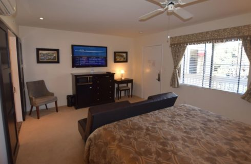 Bedroom with dark wood dresser and desk, dark brown leather couch, flat-screen TV mounted on wall, and white ceiling fan