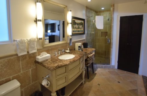 Bathroom with tiled walls, floor, and shower, large wooden vanity with small makeup table and granite countertops