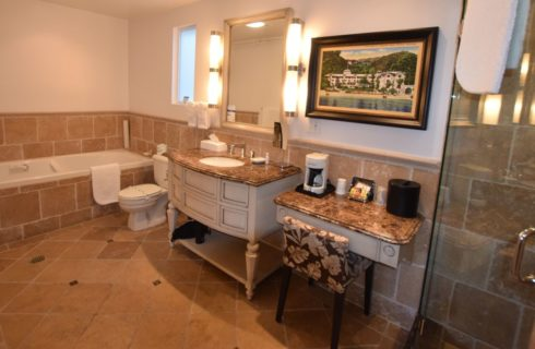 Bathroom with tiled walls, floor, and tub, large wooden vanity with small makeup table and granite countertops