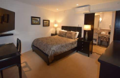 Bedroom with dark wood furniture, light brown bedding, large flat-screen TV mounted on wall