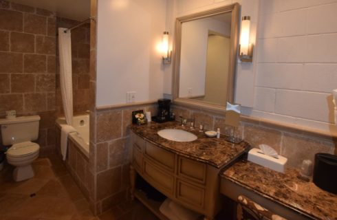 Light tan tiled bathroom and tub with wooden vanity and granite countertop