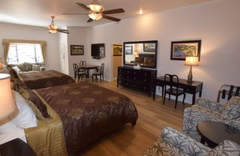 Very large room with two king beds, couch, table with chairs, desk with chair, two upholstered chairs, and larger dresser