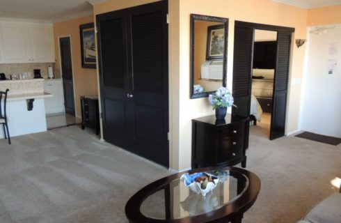 Living space with couch, coffee table, and kitchen with full-size fridge, microwave, stove top with oven and coffee maker