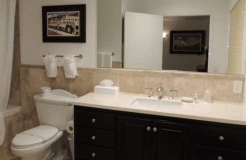 Bathroom with light tan tile on walls, floor, and tub with dark wood vanity and granite countertop