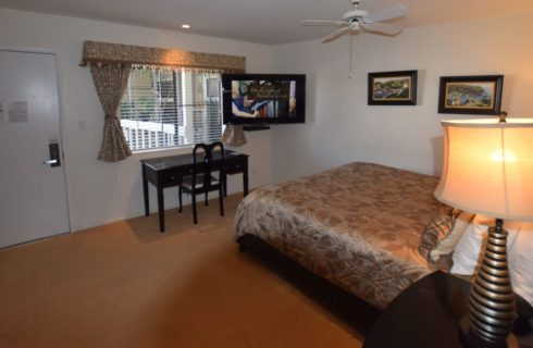 Bedroom with dark wood furniture, black and gold lamps, flat-screen TV mounted on wall near window, and white ceiling fan