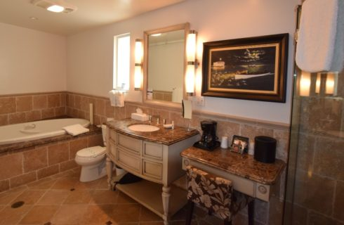 Bathroom with light tan tiled floors, tub, and walls with large vanity and granite counter tops