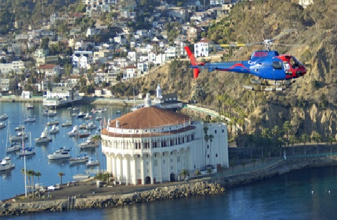 Blue and red helicopter flying over the water above Catalina Casino.