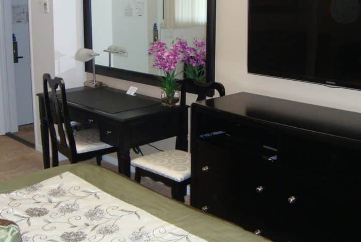 Bedroom with dark wood furniture, desk with two chairs, dresser, and large flat-screen TV