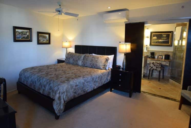 Bedroom with dark wood furniture, light brown bedding, large flat-screen TV, and view into tiled bathroom