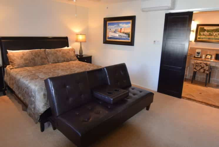 Bedroom with dark wood furniture, light tan bedding, black and gold lamps, and dark brown leather couch