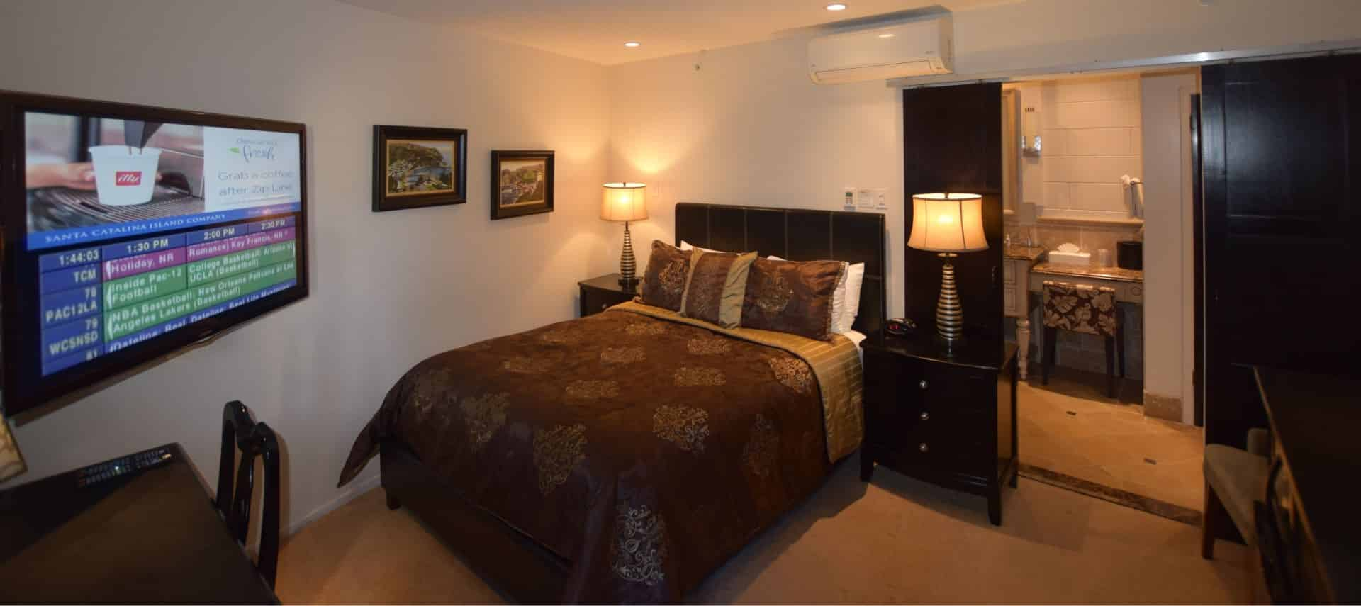 Dark wooden bed with brown and tan bedding, dark wood nightstands, and large flat-screen TV mounted on wall