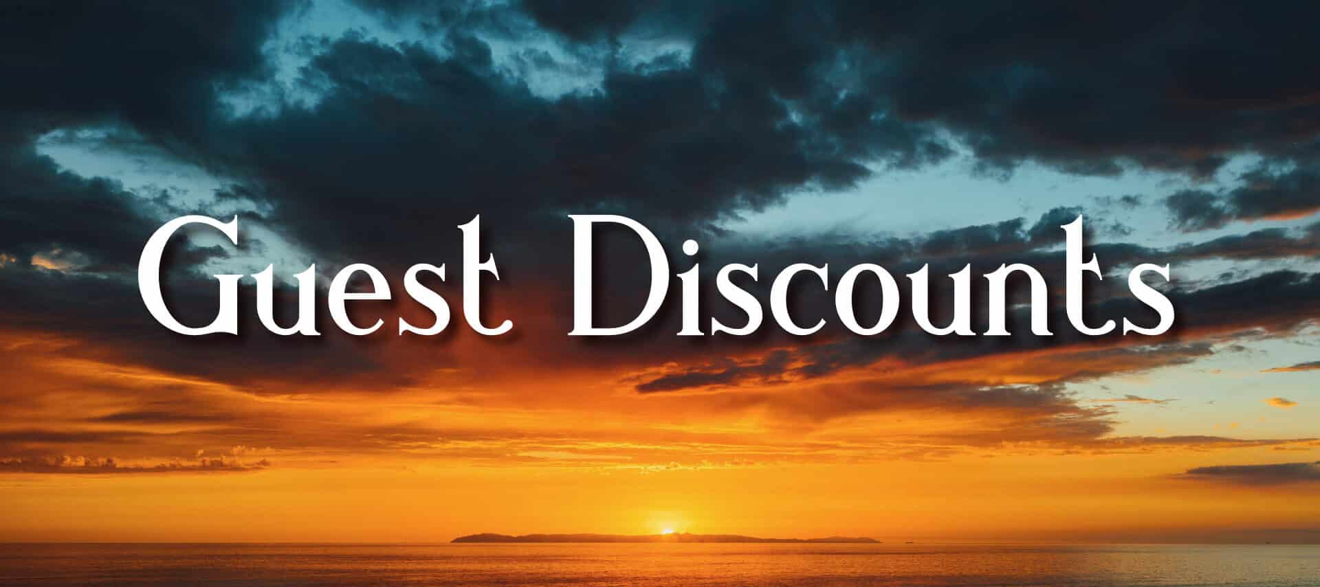 Sunset with orange and dark blue sky over ocean and small island background with text Guest Discounts in white