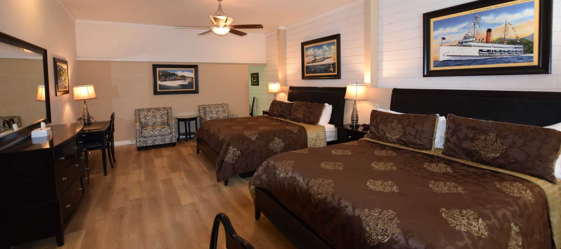 Large bedroom with dark brown furniture, two king beds with dark brown bedding, and two upholstered chairs