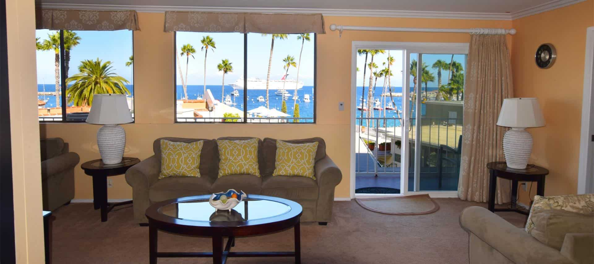 Bedroom with light brown couch with yellow pillows, wood and glass coffee table, end table with white lamp, and amazing view of the ocean and palm trees