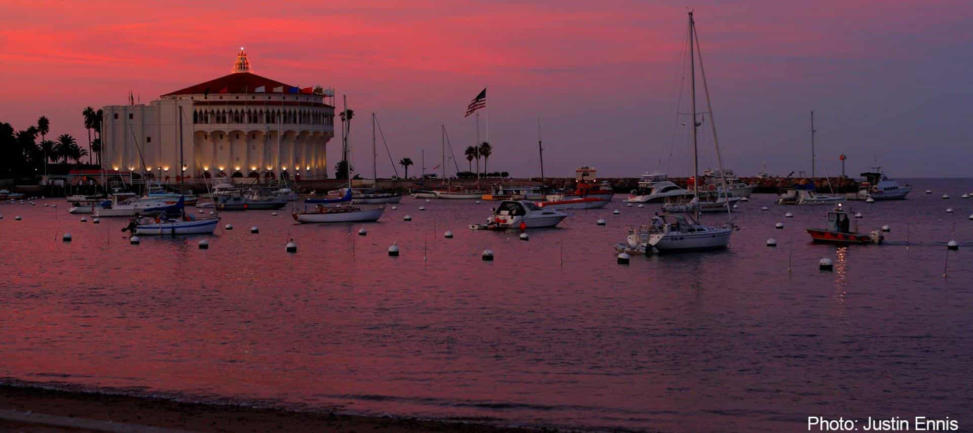 View of an ocean marina at dusk with soft purple and pink colors in the sky