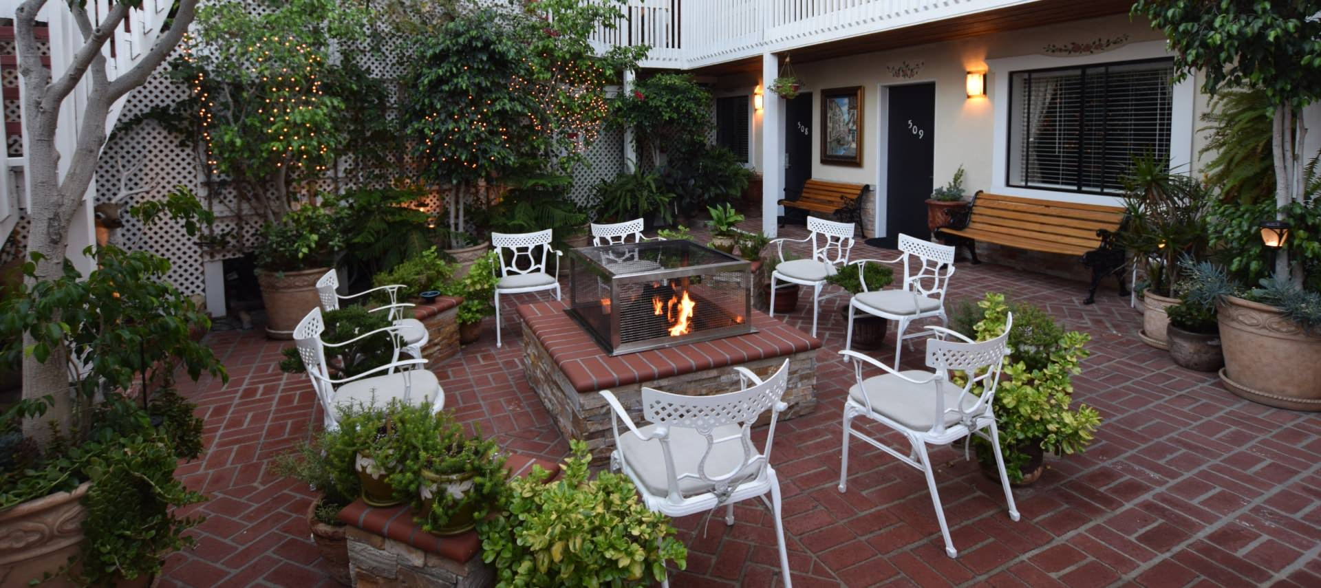 Courtyard patio with red brick and white chairs around a stone fire pit with greenery