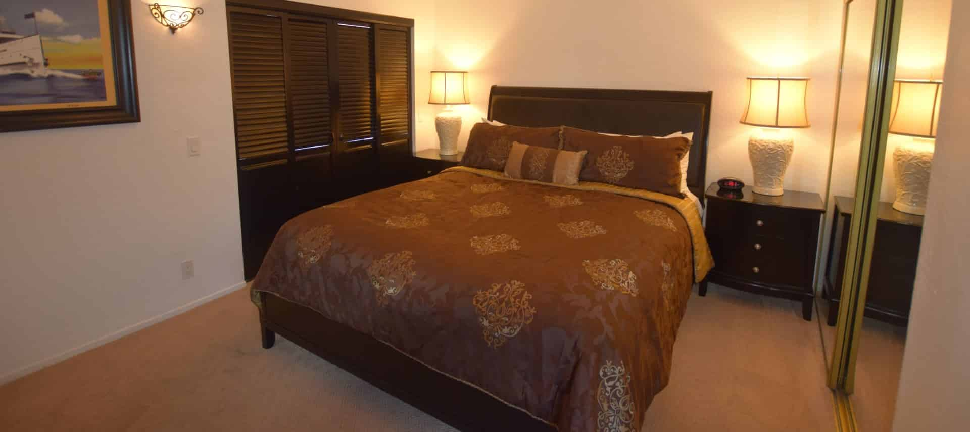 Dark wooden bed with brown and tan bedding with dark wood nightstands with white porcelain lamps