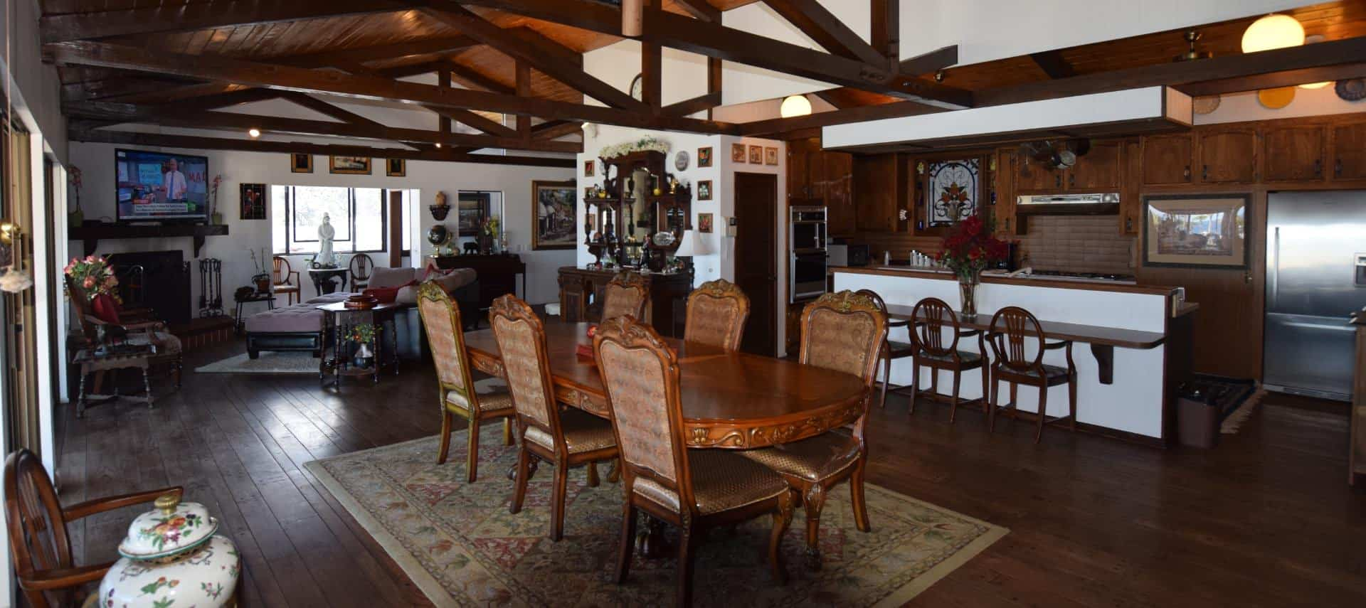 Very large living space with wood floor, ceiling, and beams including large ornate wooden dining table, kitchen area, sitting area, fireplace, and large flat-screen TV